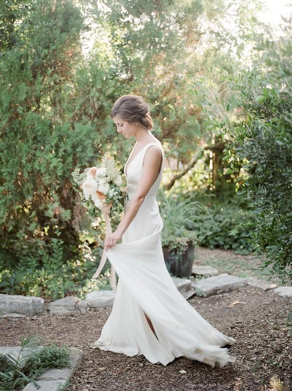 Bride walking in garden of Barr Mansion in Austin, Texas