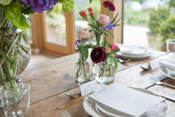 Small vases of flowers at place setting