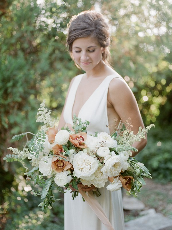 Bride holding bouquet of peach and white flowers