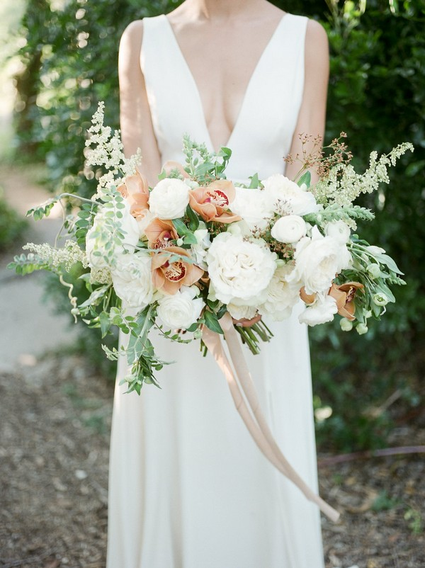 Bride holding peach and white bridal bouquet