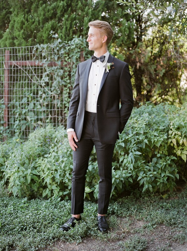 Groom wearing black suit with bow tie
