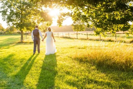 Bride and groom by trees in sunshine - Picture by Heather Jackson Photography
