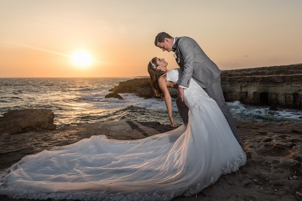 Groom leaning bride back by sea at sunset - Picture by Lee Stuart Photography