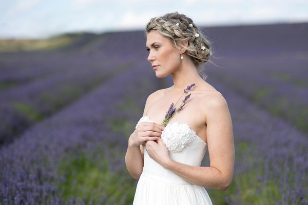 Bride holding sprig of lavender to her chest while standing in a lavender field - Picture by Eva Tarnok Photography