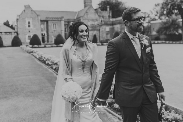 Bride and groom holding hands as they walk down driveway of wedding venue - Picture by BGS Weddings