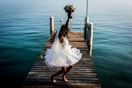 Bride in short wedding dress holding bouquet abover her head on jetty - Picture by Carine Bea
