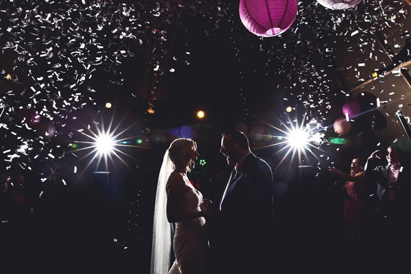 Excited bride and groom facing each other on dance floor with mouths wide open - Picture by Katie Sidell Photography