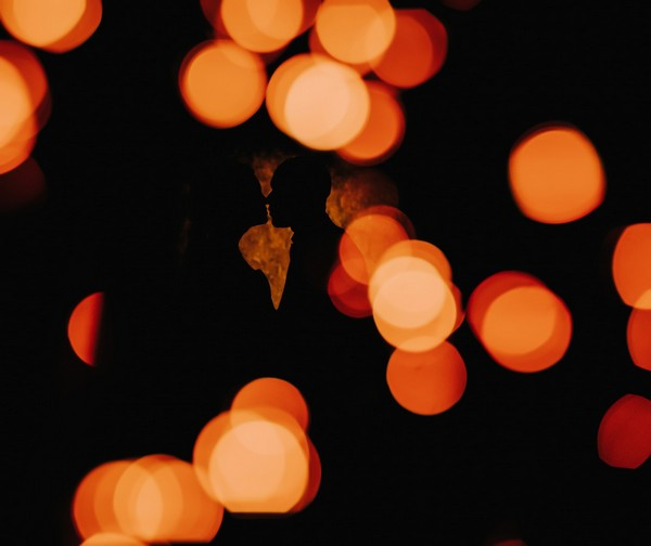 Silhouette of couple about to kiss behind spots of light - Picture by Michelle Wileman Photography