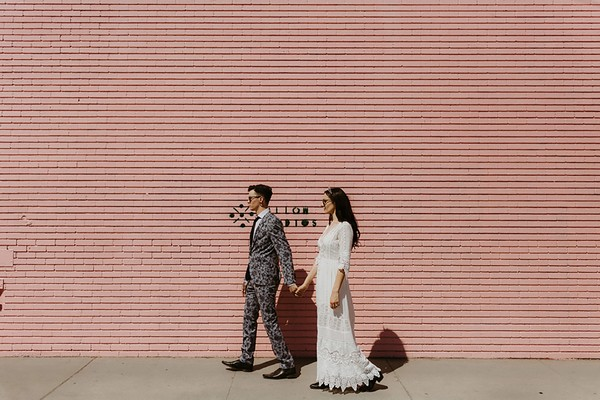 Cool bride and groom walking next to pink wall - Picture by The Hendrys Photography