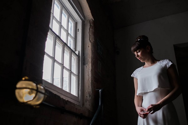 Bride standing by a window - Picture by Simon Dewey Photography