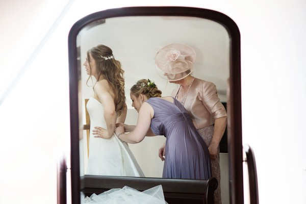 Reflection in mirror of bridesmaid doing up back of bride's wedding dress