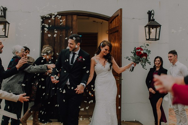 Confetti being thrown as bride and groom leave wedding ceremony