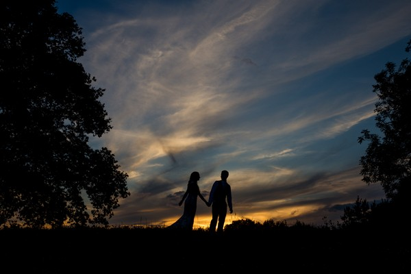 Silhouette of bride and groom between trees with dark coloured sky - Picture by Joss Denham Photography