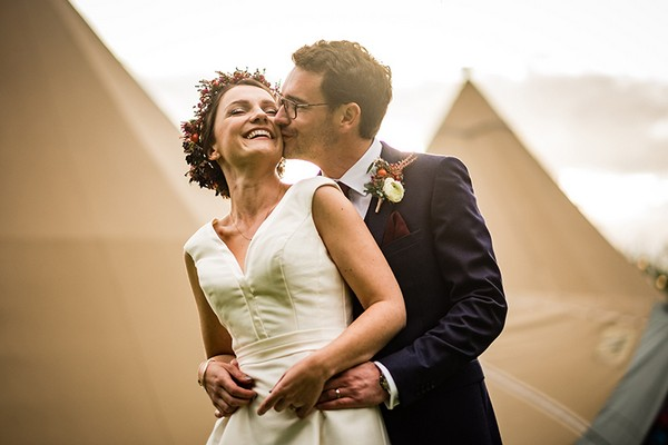 Groom kissing bride on cheek from behind in front of tipis - Picture by Linus Moran Photography