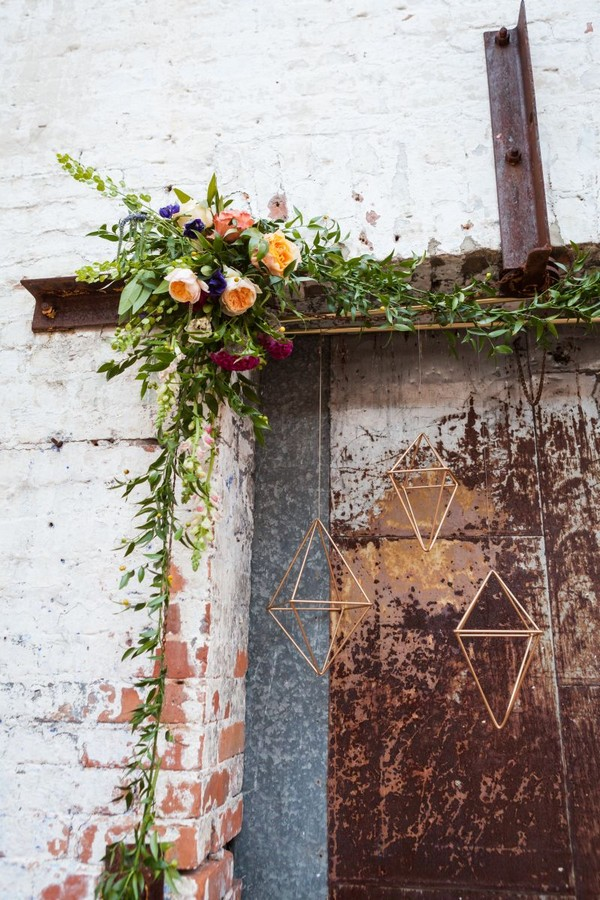 Flower and foliage arrangement over door with hanging geometric shapes