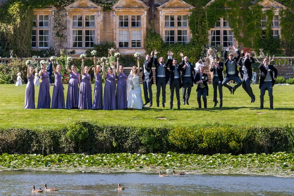 Wedding party by pond at Brympton House