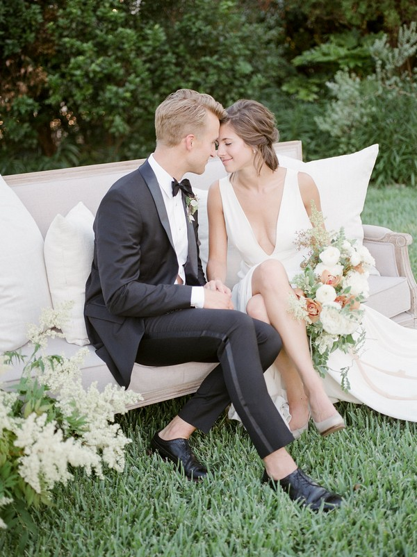 Bride and groom sitting on couch in garden