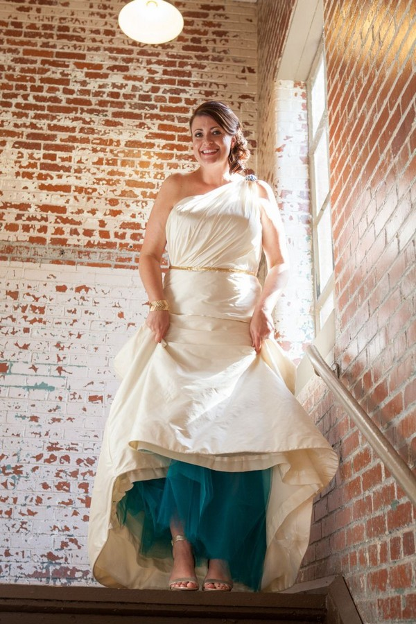 Bride lifting wedding dress to show teal underskirt