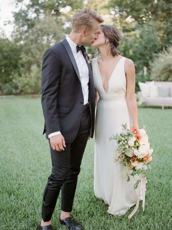 Bride and groom kissing in garden of Barr Mansion in Austin, Texas