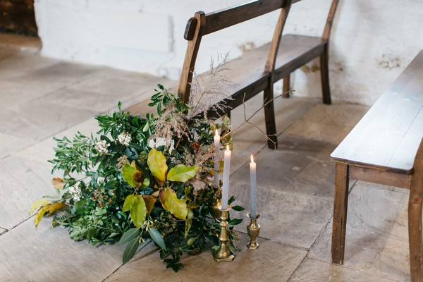 Foliage and candles by wedding ceremony chairs