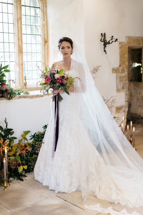 Bride with long veil holding bouquet