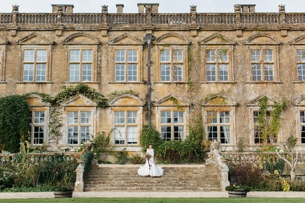 Bride on steps outside Brympton House