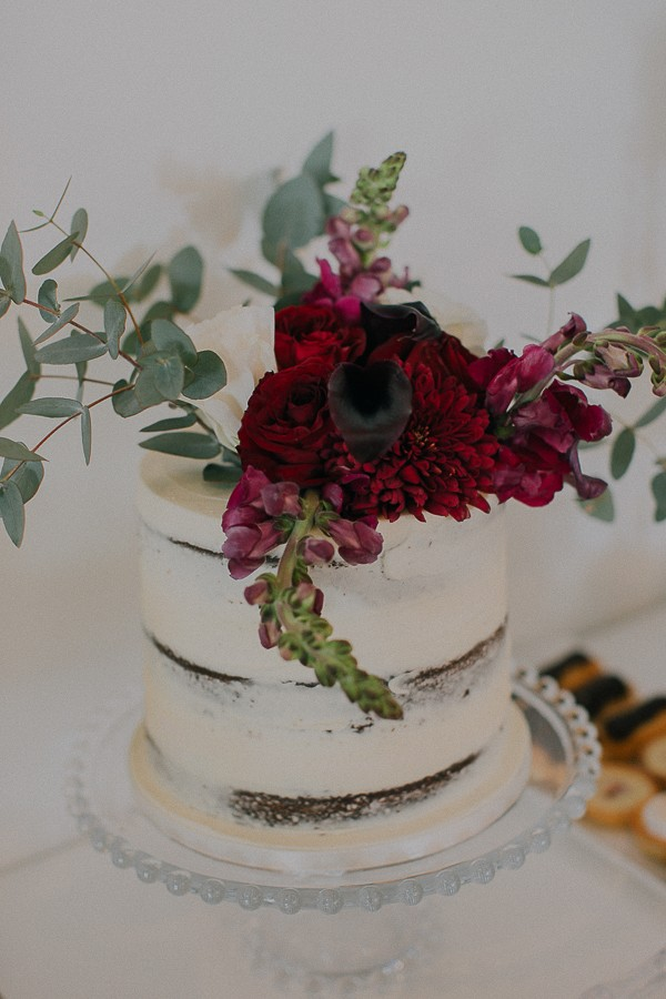Wedding cake with large red floral topper