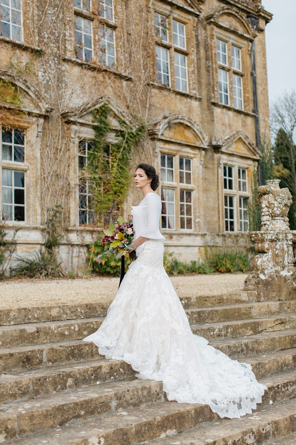 Bride with dress train trailing down steps outside Brympton House