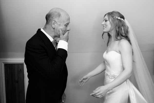 Father with hand over his mouth when he sees his daughter in wedding dress