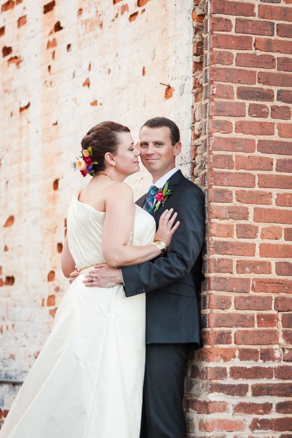 Bride and groom leaning against a wall