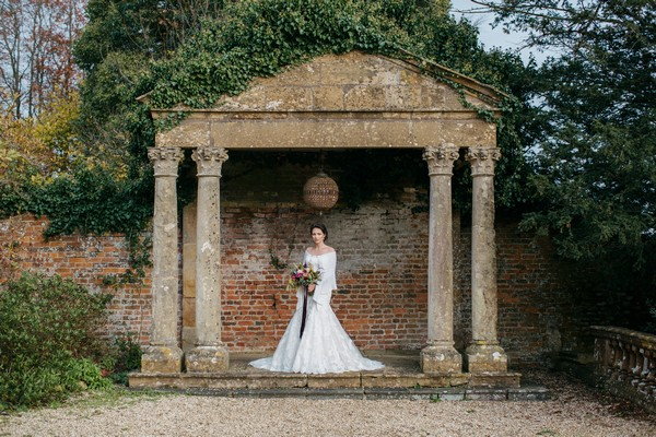 Bride under stone structure in grounds of Brympton House