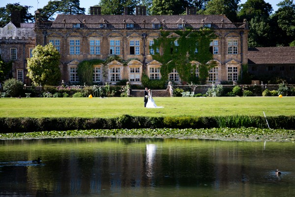 Bride and groom by pond at Brympton House