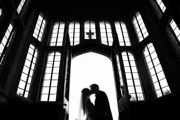 Bride and groom kissing at entrance to Brympton House