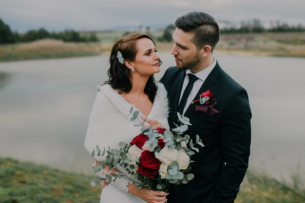 Bride holding winter bouquet looking at groom