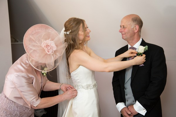Bride adjusting father's buttonhole
