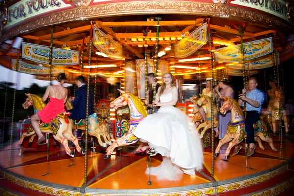 Bride on funfair carousel at Brympton House