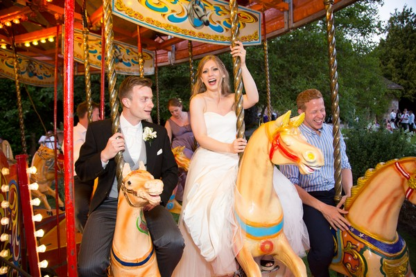 Bride and groom on funfair carousel at Brympton House