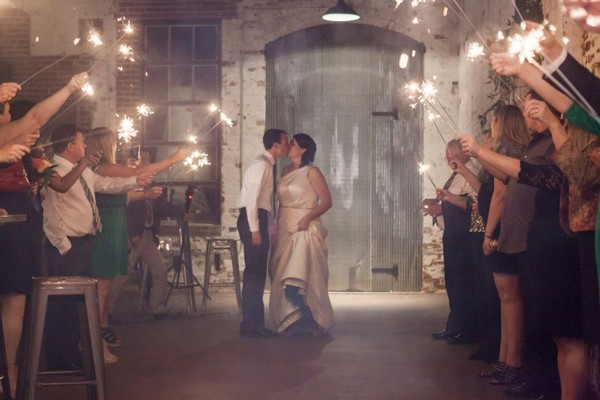 Bride and groom kissing in the middle of guests holding sparklers
