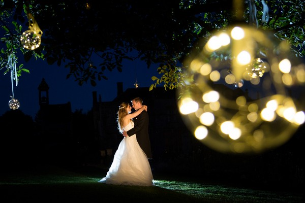 Bride and groom in garden of Brympton House at night