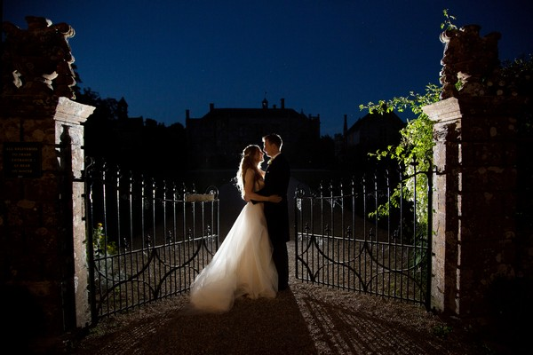 Bride and groom by Brympton House gates at night