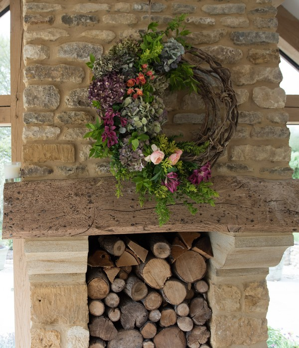 Wreath hanging over log-filled fireplace