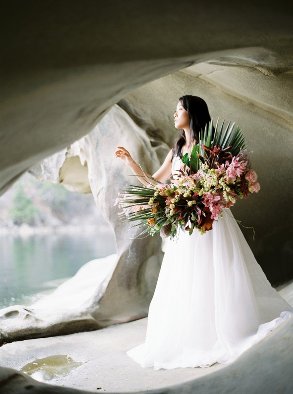 Bride holding large bouquet in cave