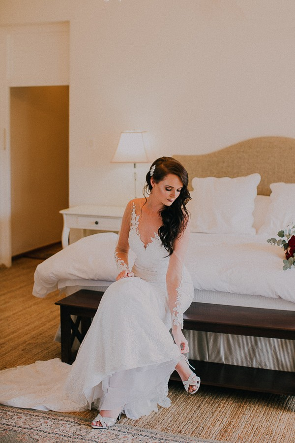 Bride sitting on bed putting shoes on