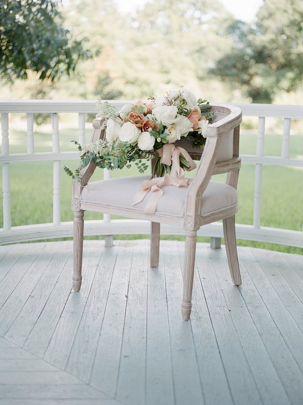 Peach and white bridal bouquet on chair