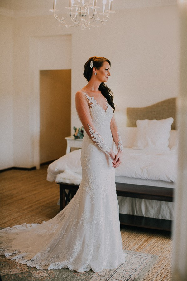 Bride standing in elegant lace wedding dress