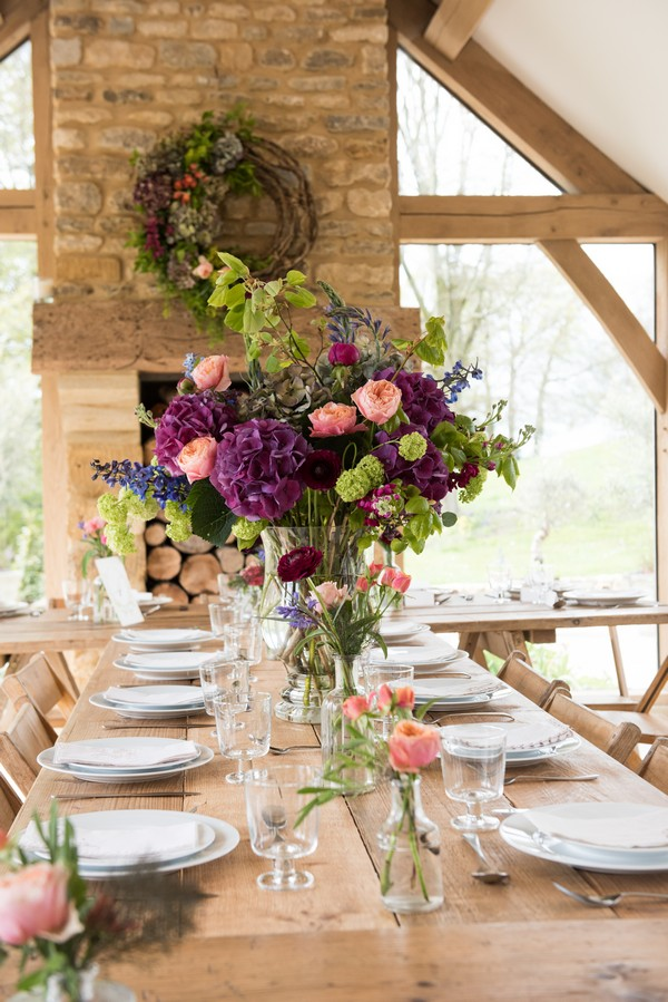 Large display of homegrown flowers on rustic wedding table