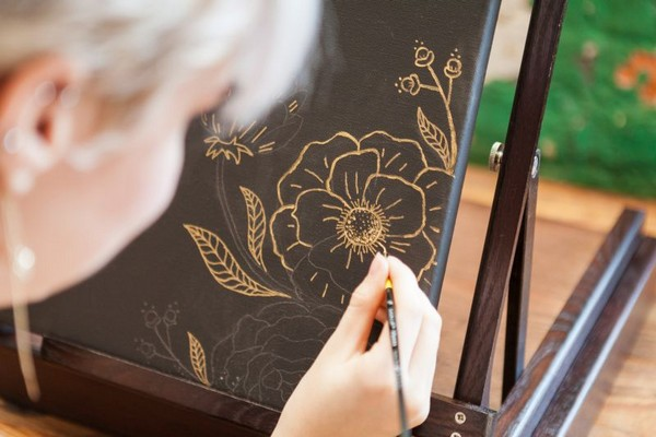 Woman drawing gold flowers on wedding guest book