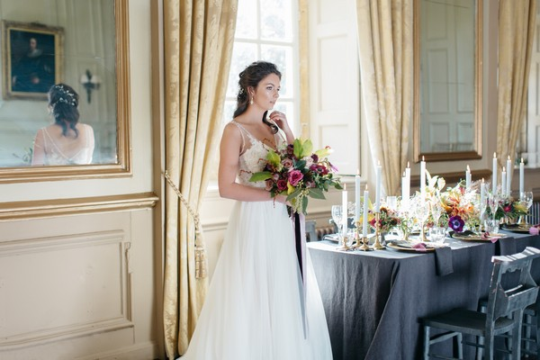 Bride holding bridal bouquet next to wedding table