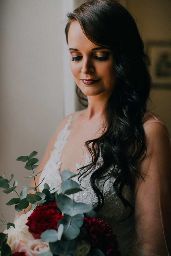 Bride with hair down hairstyle looking down at bouquet