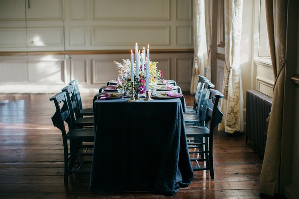 Wedding table with dark tablecloth and styling
